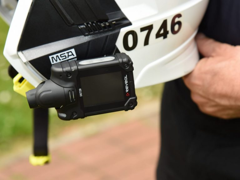 firefighter hand holding helmet with fitted video camera